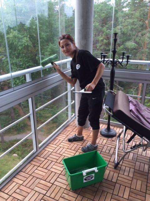 Fönsterputs tjej tvättar fönster med skrapa