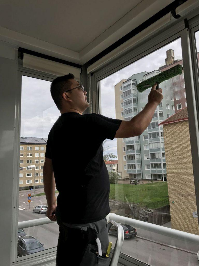 Fönsteputs kille tvättar fönster med skrapa