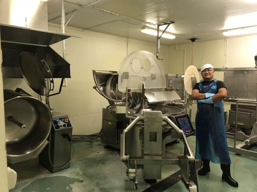 Företagstjänster Kille står bredvid storköksmaskin